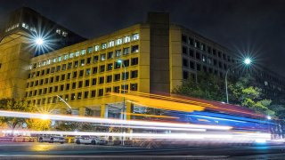 In this Nov. 1, 2017, file photo, traffic along Pennsylvania Avenue streaks past the Federal Bureau of Investigation headquarters building in Washington, D.C.