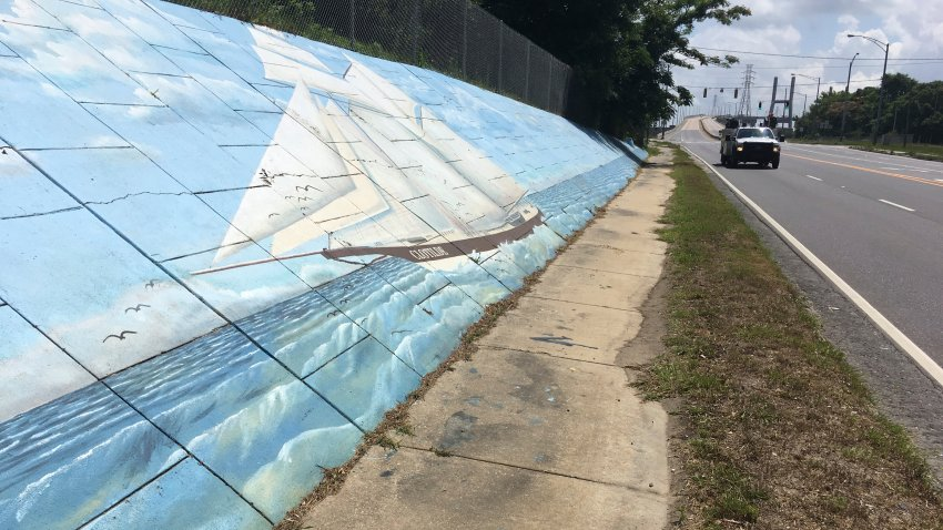 Traffic passes a mural of the last slave ship to the U.S. along Africatown Boulevard