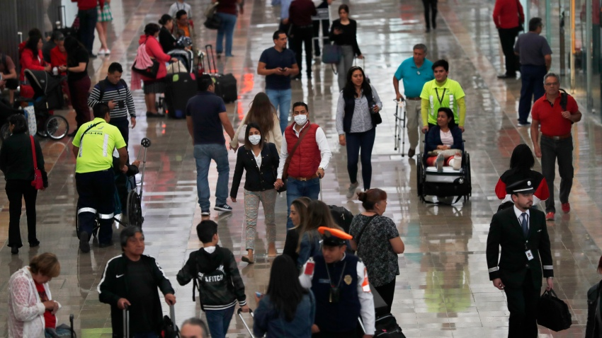 A couple wears protective masks as a precaution against the spread of the new coronavirus at the airport in Mexico City, Friday, Feb. 28, 2020.