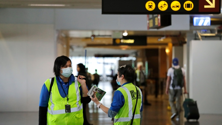 A pair of workers at Seattle-Tacoma International Airport wear masks Tuesday, March 3, 2020, in SeaTac, Wash.