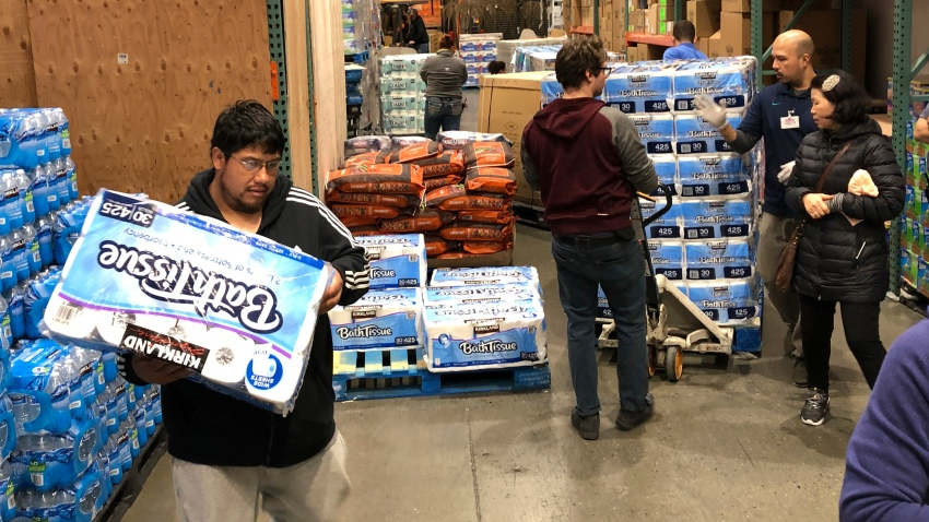Shoppers rush to pick up toilet paper that had just arrived at a Costco store, Saturday, March 7, 2020, in Tacoma, Wash.
