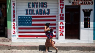 """a woman carrying a child walks past a closed courier business featuring a U.S. flag and the Spanish phrase: """"Deliveries to U.S.A"""""""