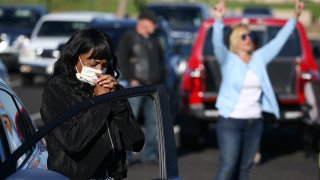 Keeping to safe social distance guidelines, worshipers pray at their own vehicles as they attend an outside drive-in Easter service at the Living Word church due to the coronavirus Sunday, April 12, 2020, in Mesa, Ariz.