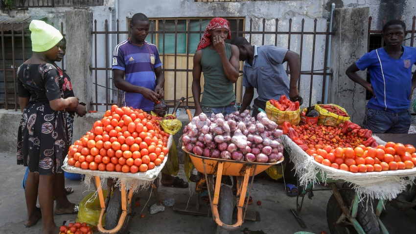 In this April 13, 2020, file photo, a woman buys tomatoes and onions from street sellers in Lagos, Nigeria. Lockdowns in Africa limiting the movement of people in an attempt to slow the spread of the coronavirus are threatening to choke off supplies of what the continent needs the most: Food.