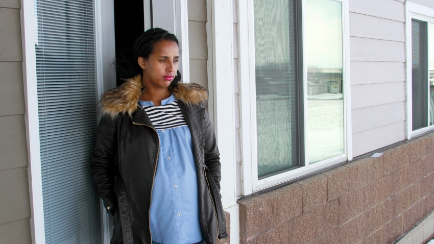 Kulule Amosa steps out of the apartment she shares with her husband who works at the Smithfield Foods pork processing plant in Sioux Falls, S.D.
