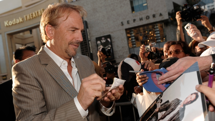 """Kevin Costner looks down at a photo of himself from the film """"Bull Durham"""" as he signs autographs in Los Angeles."""