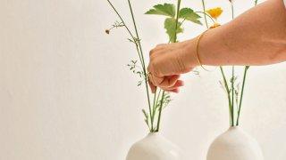 A woman arranges flowers in a vase