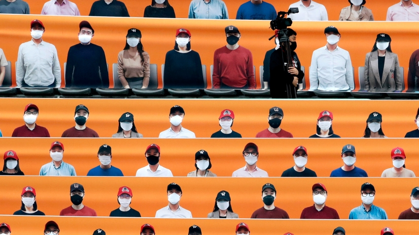 A TV cameraman walks through the spectators' seating which are covered with pictures of fans, before the start of a regular season baseball game between Hanwha Eagles and SK Wyverns in Incheon, South Korea, Tuesday, May 5, 2020. South Korea's professional baseball league start its new season on May 5, initially without fans, following a postponement over the coronavirus.