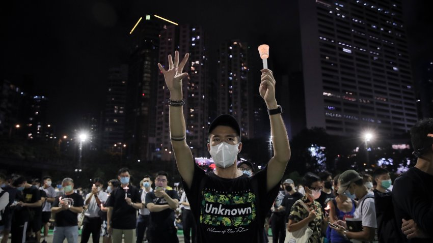 "Participants gesture with five fingers, signifying the ""Five demands - not one less"" during a vigil for the victims of the 1989 Tiananmen Square Massacre at Victoria Park in Causeway Bay, Hong Kong, Thursday, June 4, 2020. China is tightening controls over dissidents while pro-democracy activists in Hong Kong and elsewhere try to mark the 31st anniversary of the crushing of the pro-democracy movement in Beijing's Tiananmen Square."