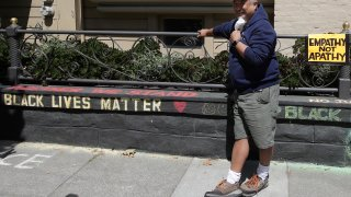 "James Juanillo poses next to chalk written outside of his home in San Francisco, Sunday, June 14, 2020. The CEO of a cosmetic company issued an apology Sunday after she and her husband confronted Juanillo and threatened to call police because he stenciled ""Black Lives Matter"" in chalk on his San Francisco property, as the couple asserted that they know Juanillo doesn't live there and is therefore breaking the law."