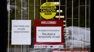 """A """"Temporarily Closed"""" sign is seen in front of a store amid the coronavirus pandemic on May 14, 2020, in Arlington, Virginia."""