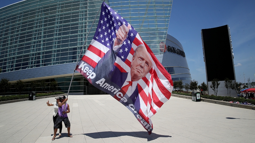 Two Trump supporters pose for photos with a giant Trump flag outside BOK Center, site of Trump's first political rally since the start of the coronavirus pandemic, June 18, 2020 in Tulsa, Okla.