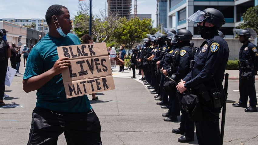 A man holds a Black Lives Matter sign in front of the San Diego Police in downtown San Diego, California on May 31, 2020 as they protest the death of George Floyd.