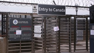 Signs hang at the entrance to Canada via the Rainbow Bridge, March 18, 2020, in Niagara Falls N.Y. President Donald Trump and Canadian Prime Minister Justin Trudeau have agreed to close the U.S.-Canada border to non-essential travel in order to slow the spread of the COVID-19 coronavirus.