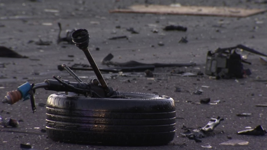 A car tire and debris lay on the road following a car crash.