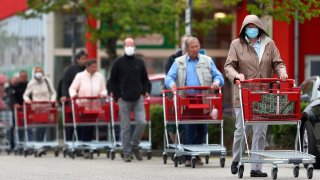People wearing protective masks queue up to go in a garden store in Munich, Germany, Monday, April 20, 2020.
