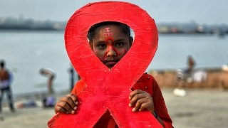A young girl holds a placard of a red ribbon during the World AIDS Day