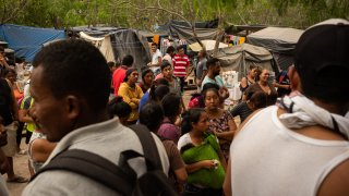 In this March 20, 2020, file photo, asylum seekers stand for a headcount at a makeshift migrant camp in Matamoros, Tamaulipas state, Mexico.