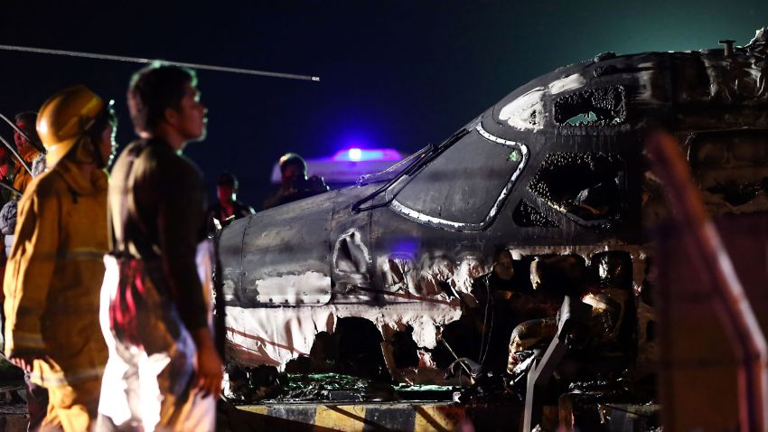 Rescuers stand next to the wreckage of a Westwind aircraft after it caught on fire during takeoff at Manila international airport in Manila