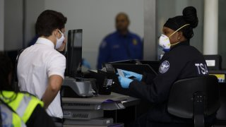 TSA agent in mask at LAX speaks with traveler in mask.