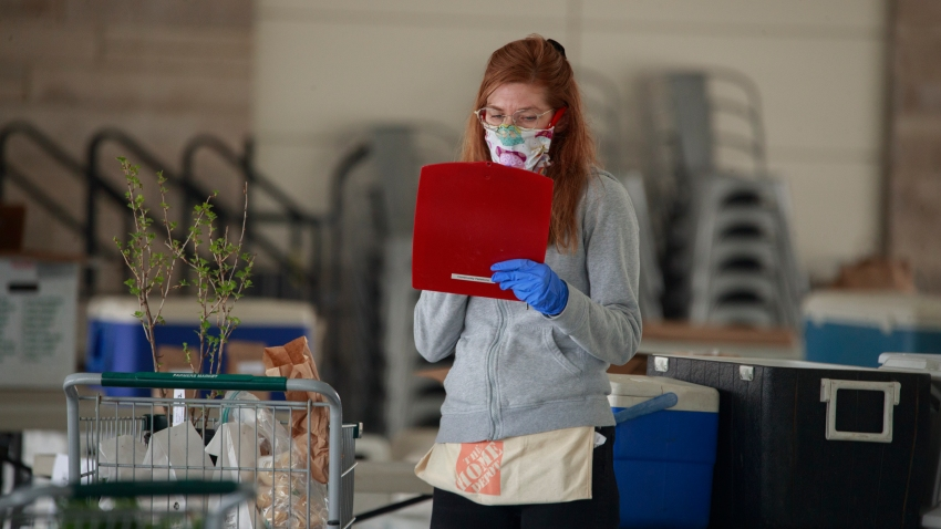 A worker wearing a face mask prepares an internet order for customers of the Bloomington Community Farmers' Market where food is being distributed in a drive-thru arrangement at the Switchyard Pavilion