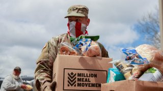 A member of the Indiana National Guard wearing an American flag balaclava carries food to a vehicle