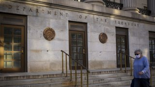 A pedestrian wearing a protective mask passes the U.S. Treasury building