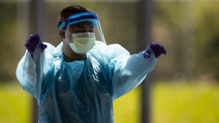 A medical professional adjusts his protective equipment as he walks through a coronavirus (covid-19) drive thru test site