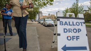 Ohio voters walk to drop off their ballots at the Board of Elections in Dayton, Ohio on April 28, 2020.