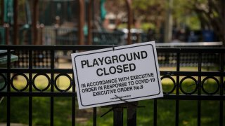 A closed sign is displayed in front of a playground in Chicago