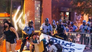 Protester crouching on the ground with police behind them
