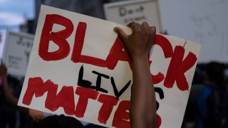 A person holds up a placard that reads, 'Black lives matter'