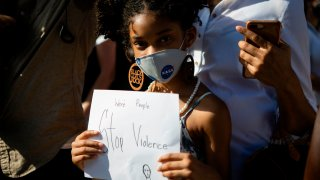 A young girl wearing a facemask holds a sign during a rally in Coral Gables, Florida on May 30, 2020 in response to the recent death of George Floyd, an unarmed black man who died while being arrested and pinned to the ground by a Minneapolis police officer.
