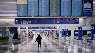 A worker walks through a baggage claim area at a nearly-empty O'Hare International Airport