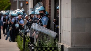 Police stand guard as demonstrators take part in a protest in Uptown