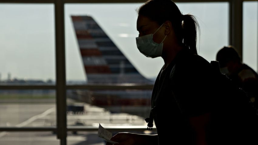 A traveler wearing a protective mask walks past an American Airlines Group Inc. plane tail fin at Ronald Reagan National Airport (DCA) in Arlington, Virginia, U.S., on Tuesday, June 9, 2020. U.S. airline shares last week headed for a record weekly gain as investors bet that travel demand was poised to rebound on signs that passengers were returning after the Covid-19 pandemic devastated demand.