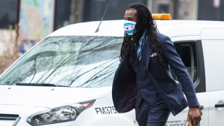 A person wearing a face mask walks down a mostly dormant Michigan Avenue