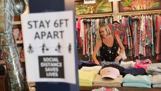 In this May 4, 2020, file photo, Beth Beall shops at the Tommy Bahamas store in Stuart, Florida, as the state enters phase one of the plan to reopen.