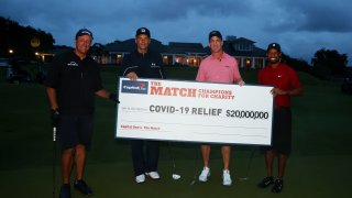 Tiger Woods and former NFL player Peyton Manning celebrate defeating Phil Mickelson and NFL player Tom Brady of the Tampa Bay Buccaneers on the 18th green during The Match: Champions For Charity at Medalist Golf Club on May 24, 2020 in Hobe Sound, Florida.