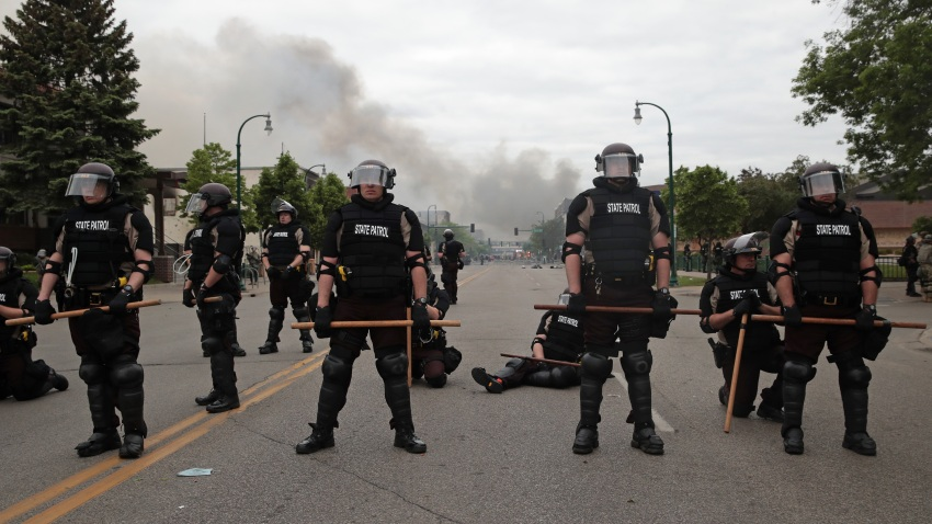 Police officers block a road on the fourth day of protests in Minneapolis