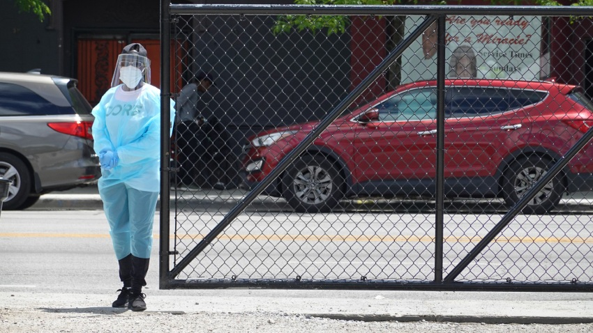A worker directs residents at a mobile COVID-19 testing site set up on a vacant lot in the Austin neighborhood