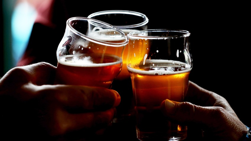 In this Feb. 7, 2014, file photo, Russian River Brewing Company customers clink their glasses while drinking the newly released Pliny the Younger triple IPA beer in Santa Rosa, California.
