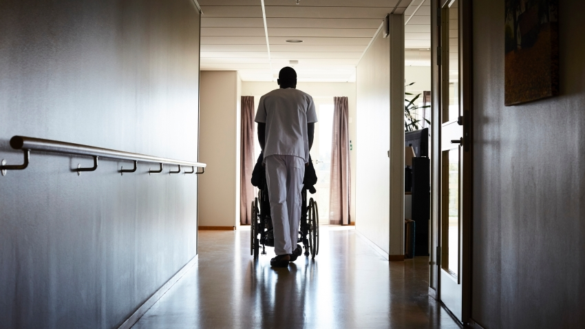 View of male nurse pushing senior man on wheelchair