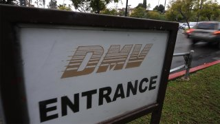 "A white sign reads ""DMV Entrance"" as a car is seen in the background"