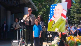 Santa Cruz Sheriff Jim Hart stands next to a photo of fallen Sgt. Damon Gutzwiller, next to the officer's pregnant widow and child as more than a thousand people gather outside the Santa Cruz County Sheriff-Coroner's Office to pay their respects in Santa Cruz, Calif., Sunday, June 7, 2020.