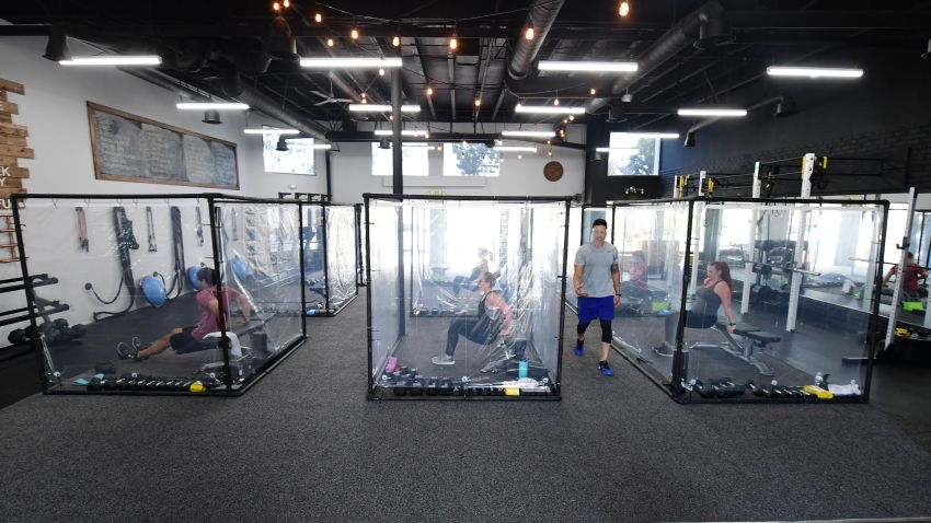 Peet Sapsin leads a class at Inspire South Bay Fitness with students behind plastic sheets in their workout pods while observing social distancing on June 15, 2020 in Redondo Beach, California, as the gym reopens under California's coronavirus Phase 3 reopening guidelines.