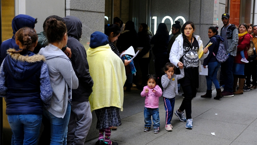 In this Jan. 31, 2019, file photo, hundreds of people overflow onto the sidewalk in a line snaking around the block outside a U.S. immigration office with numerous courtrooms in San Francisco.