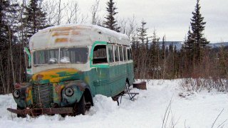 """This March 21, 2006 file photo shows the abandoned bus where Christopher McCandless starved to death in 1992 on Stampede Road near Healy, Alaska. An Italian man suffering from frostbite and four other tourists were rescued in the Alaska wilderness after visiting the abandoned bus that's become a lure for adventurers since it was featured in the """"Into the Wild"""" book and movie. Alaska State Troopers say the five were rescued Saturday, Feb. 22, 2020 from a camp they set up after visiting the bus on the Stampede Trail near the interior town of Healy. Sean Penn's movie """"Into the Wild"""" and Jon Krakauer's book of the same name is causing people from all over the world to retrace McCandless's steps to the 1940s-era International Harvester bus near Healy, Alaska where his body was found."""