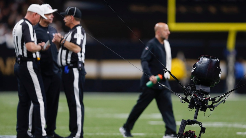 Referees confer as a malfunctioned SkyCam sits on the field, causing a stoppage the NFL wild-card playoff football game between the New Orleans Saints and the Minnesota Vikings