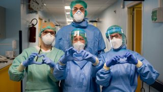 Nurses in Italy dressed in surgical gowns, gloves and protective gear making heart signs to the camera